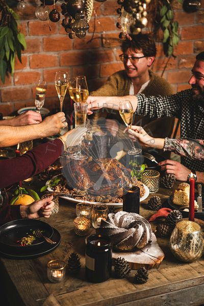 People clinking glasses over Christmas festive table with dinner