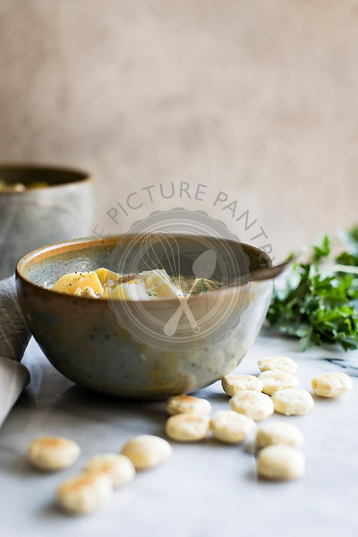 Potato, leek and bacon soup in a ceramic bowl with mini scones.