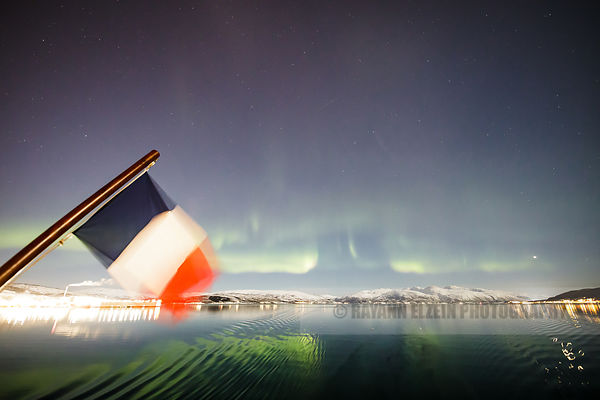 The northern lights reflecting on the sea in a fjord just before entering Tromso, Norway