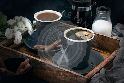 Cups of black and white coffee with chocolate cookies on a wooden tray.