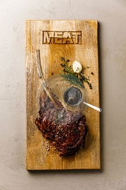 Barbecue grilled Tomahawk Steak on bone on wood serving board