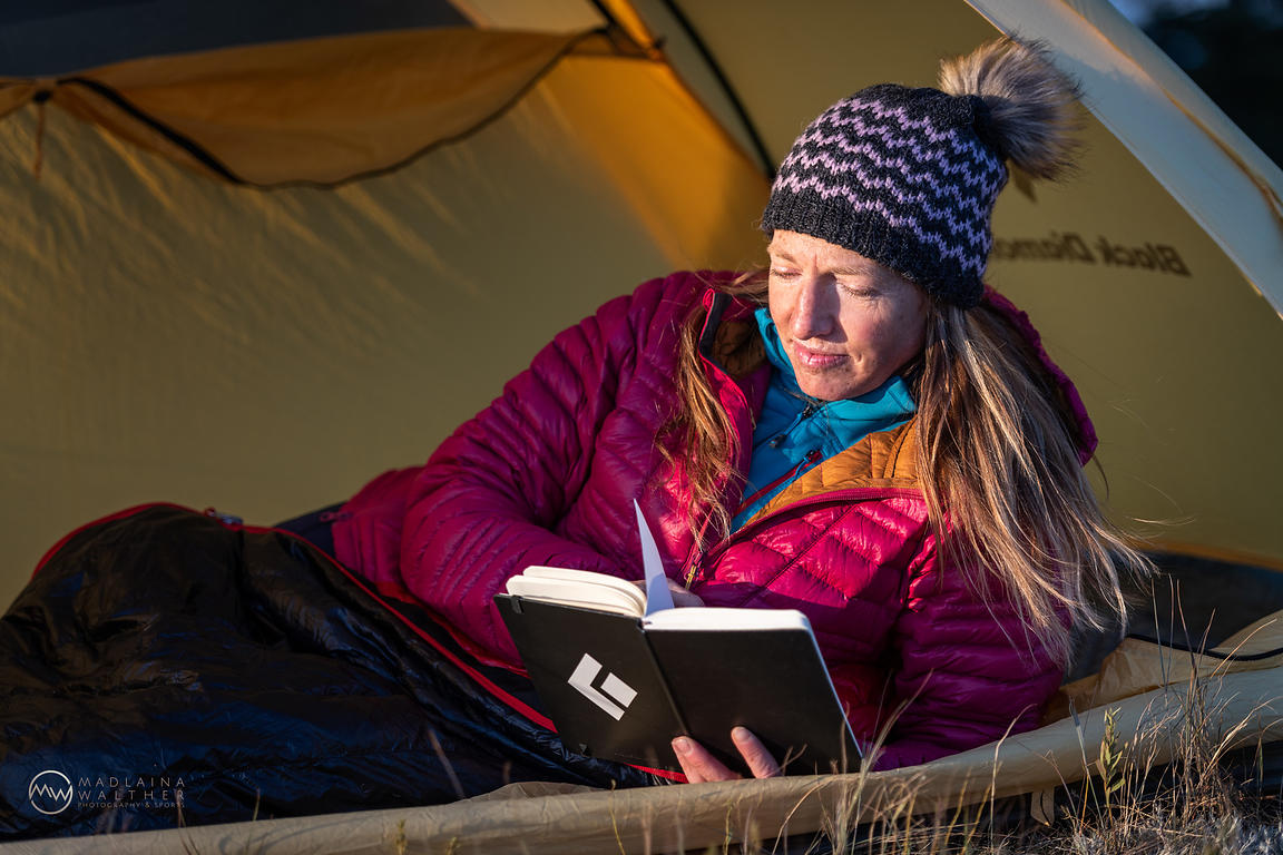 Jessica Baker lying in her tent and enjoying the last rays of sun while reading. Jackson Hole, Wyoming, USA.