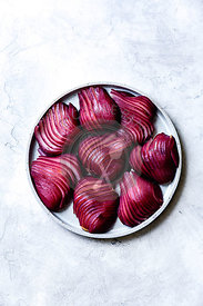 Sliced red wine poached pears on a plate.