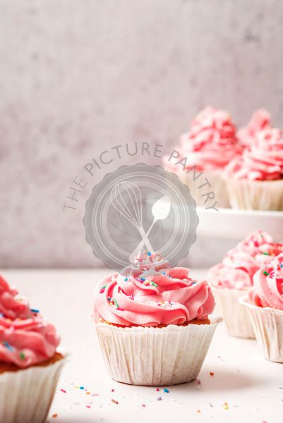 Classic pink vanilla cupcakes with vanilla butter cream frosting and sprinkles.