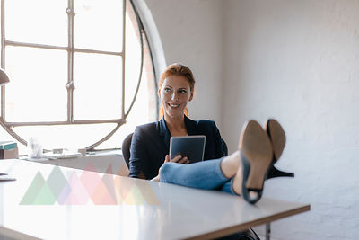 Businesswoman using tablet with feet on desk in office