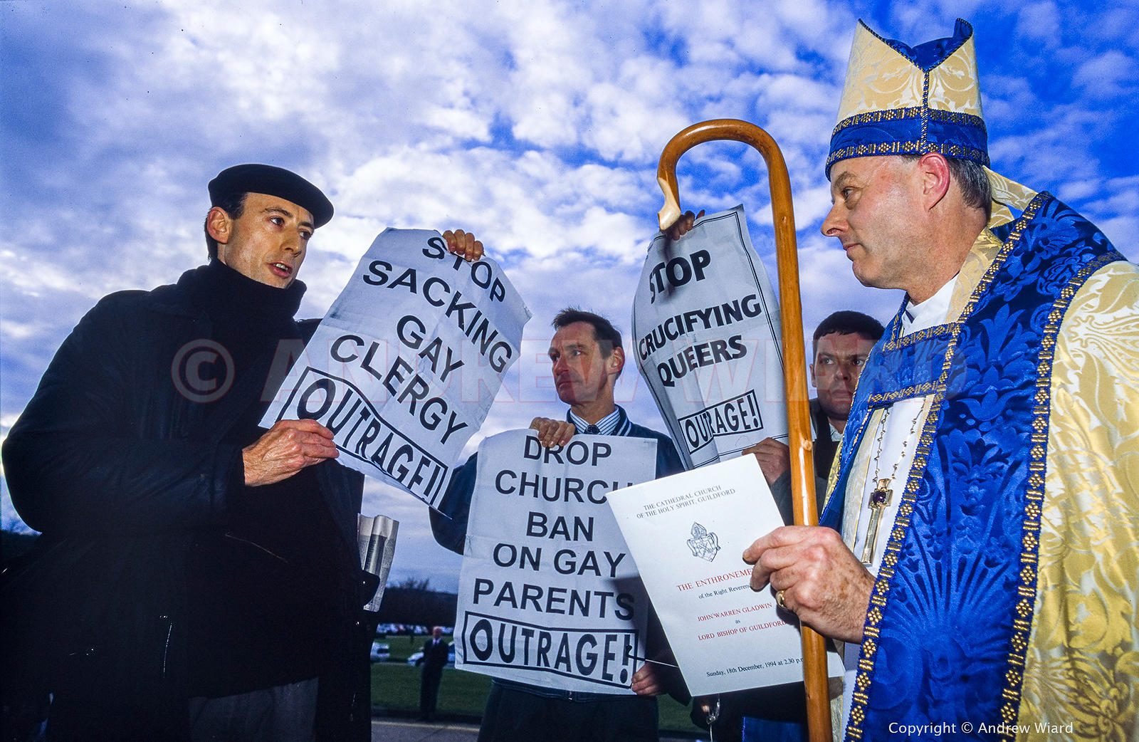 England, UK. 18.12.1994. Guildford. Peter Tatchell & OutRage demonstrators waylay the Bishop of Guildford as he arrives for h...