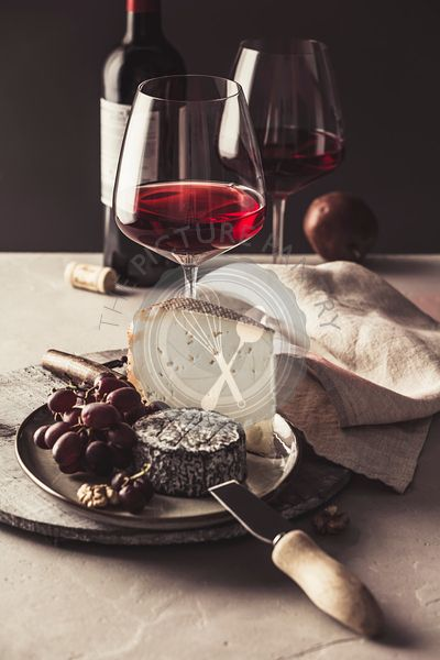 Red wine and cheese plate with fruits and nuts