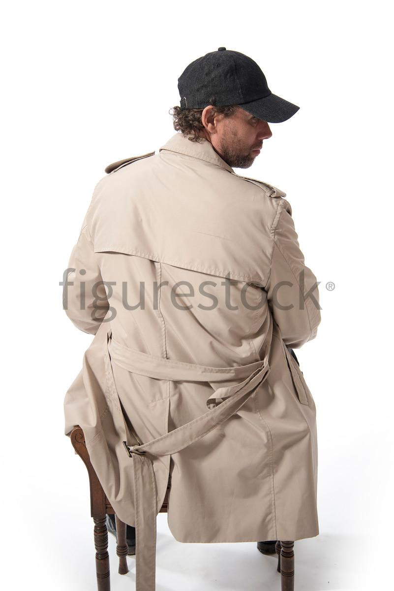 A Figurestock image of a sitting Mystery Man in a Mak and cap, from behind – shot from mid level.