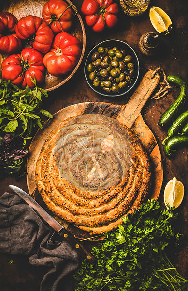 Flat-lay of Turkish borek pie with spinach filling and vegetables