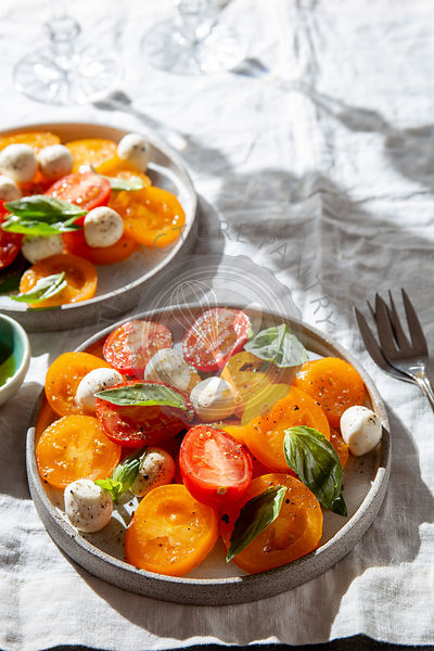 Italian caprese salad with red and yellow tomatoes, mozzarella and basil