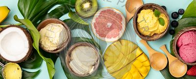 Tropical fruits and plants with variety of ice cream in coconut shells