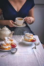 Cream puffs pastry and woman drinking a cup of tea
