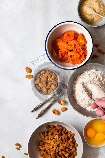 Ingredients for a healthy wholemeal fruit cake with a woman's hand spooning flour into a bowl.