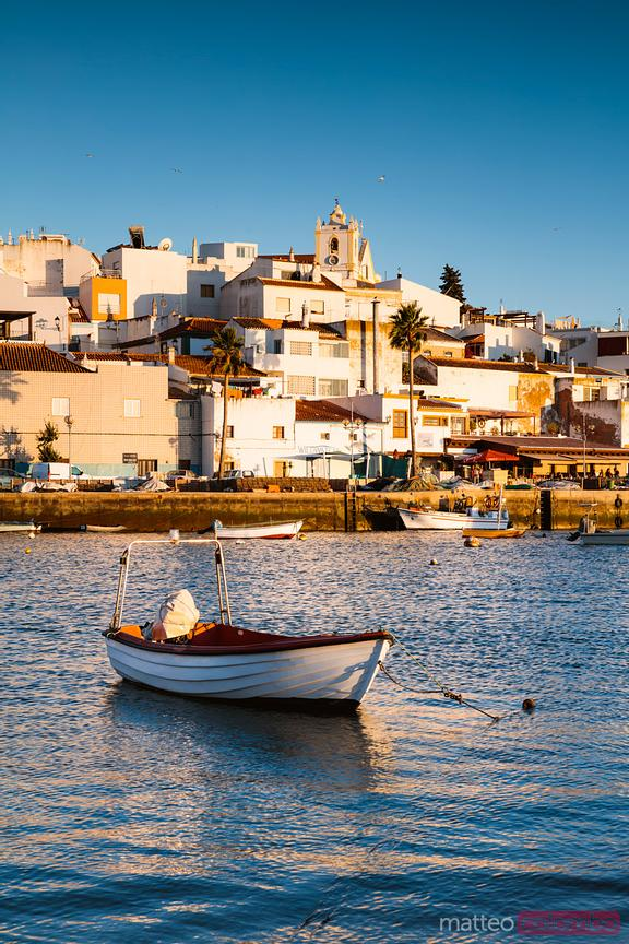 Fishing boat and town at sunset, Ferragudo, Portugal