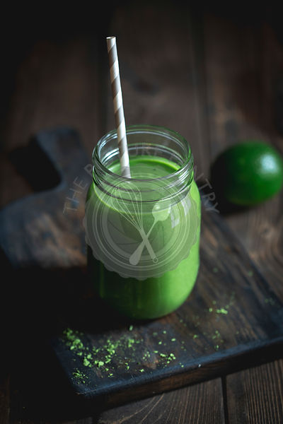 A green smoothie in a mason jar with a straw.