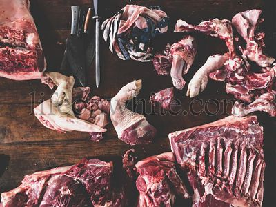 meat raw assortment and knife on the butcher's dark wooden working table. Top view.