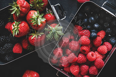 Flat-lay of fresh berries in lunchboxes over dark background, close-up