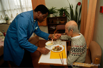 Old Asian man being helped with his food at council run residential home, Hackney, London.