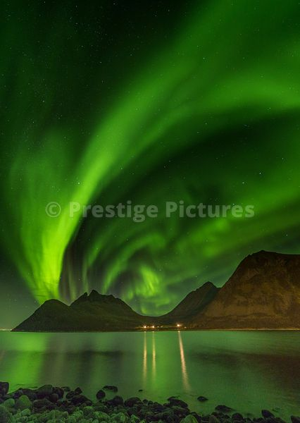 Dramatic Northern Lights in the sky and over the waters at Gryllefjord, Norway