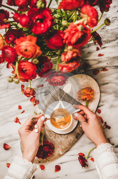 Womans hand holding cup of coffee over red flowers bouquet