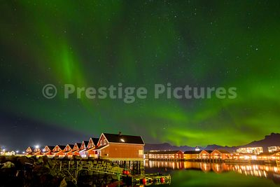 Northern Lights in the sky over typical Norwegian red houses reflecting in the harbour waters in Svolvær, Norway