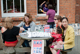 #74621,  Table selling items to raise money for the Summerhill Trust at the reunion for Summerhill School's 90th birthday cel...