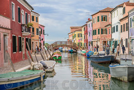 BURANO, ITALY - NOVEMBER 25, 2017: Canal boats and beautiful coloured houses in Burano, Venice, Italy.