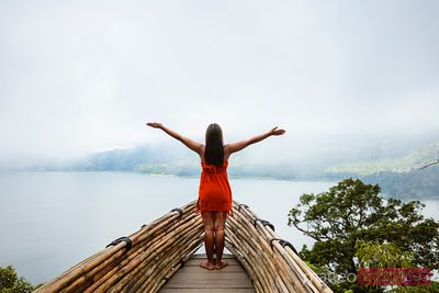 Woman rejoicing on platform over lake, Bali, Indonesia