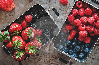Flat-lay of fresh berries in metal lunchboxes over grey background