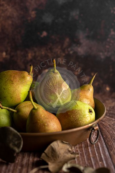 Fresh raw pears in a copper baking pan
