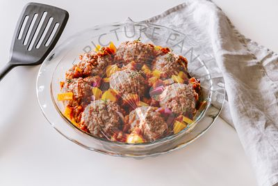 Ground beef and rice meatballs with veggies in the making ready for oven