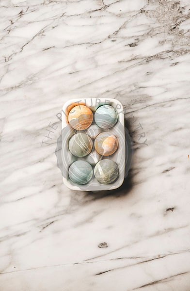 Dyed Easter eggs in white ceramic holder over marble background