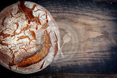 Artisan sourdough bread on wooden vintage board with blur and copy space
