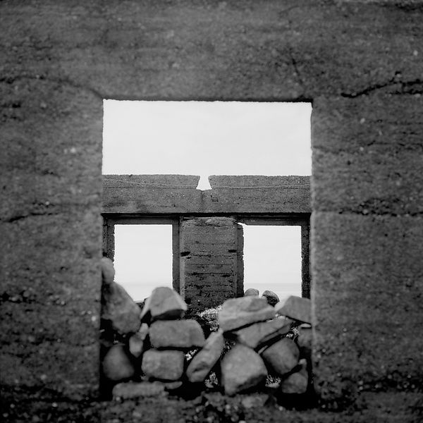 Window blocked with rocks in an abandoned house on the North side of the Island
