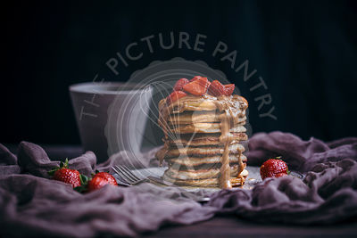 Stack of pancakes topped with strawberries, peanut butter and maple syrup