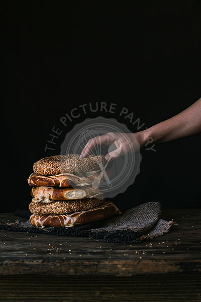 A Women's Hand Taking Bagel on a Black Background