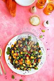 Roasted Potato Kale Salad with Cilantro Mint Vinaigrette photographed on a pink background