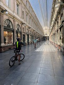 Brussels, Belgium, April 25, 2020 - two cyclist inside the empty luxury glazed shopping arcade Les Galeries Royales Saint-Hub...