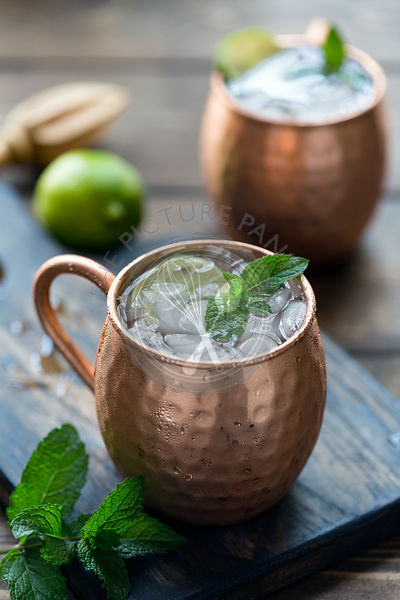Moscow mule recipe in a copper mug, garnished with lime and mint.