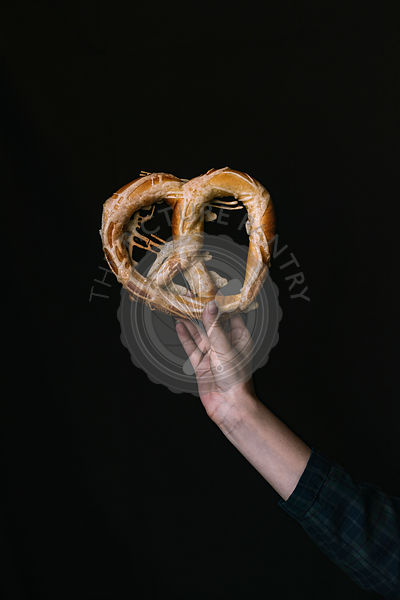A Hand with a Pretzel on a Black Background