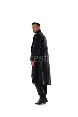 A Figurestock image of a man in a long black winter coat, walking and looking over his shoulder – shot from low level.