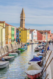 BURANO, ITALY - NOVEMBER 25, 2017: The leaning bell tower and beautiful coloured houses in Burano, Venice, Italy.