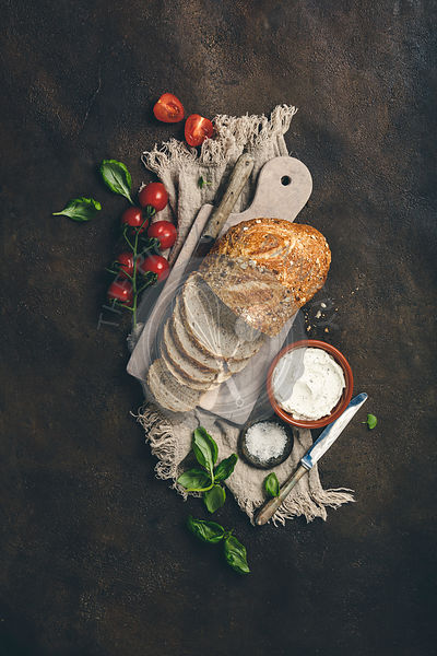 Ingredients for healthy home made sandwiches. Wholegrain bread, cream cheese, tomatoes and basil.