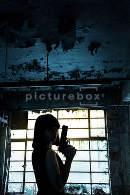 A silhouette of a mystery woman with a gun, standing in front of a dirty window, inside a damp and decaying room.