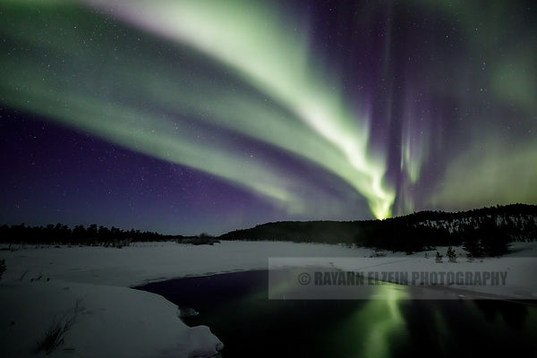 Northern lights and reflection on top of a freezing river in Inari in Lapland, Finland