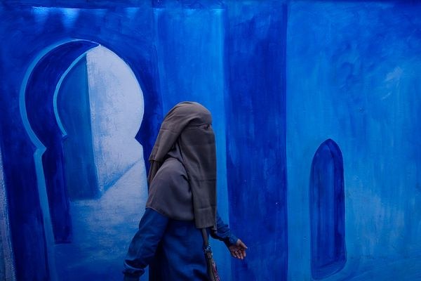 A woman wearing a niqab walks in front of a blue decorated mural in ancient medina. Chefchaouen. Djabala - Rif Region. Tanger...