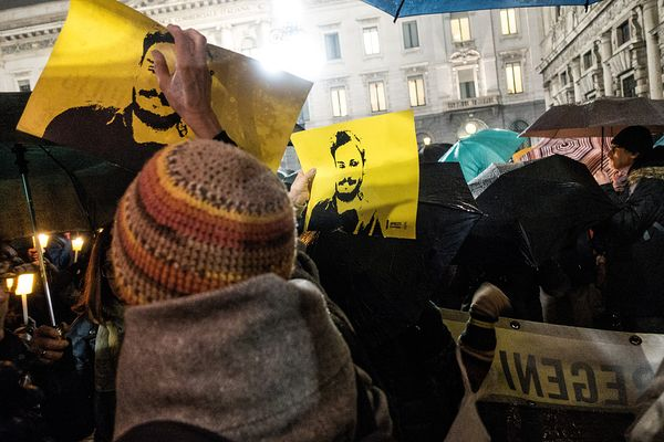 Demonstrators raising yellow signs with Mr Regeni's image on them.