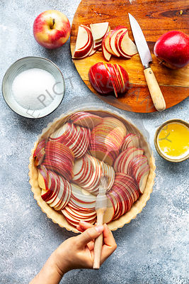 Preparation of an apple tart.Hand brushing sliced apples with melted butter