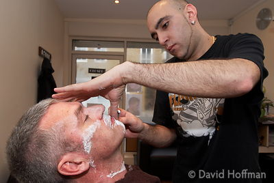 Man getting an old fashioned wet shave from Yash at Slicks barber shop in Roman Road, Bethnal Green. London