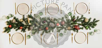Flat-lay of Christmas table setting with white dinnerware and branches